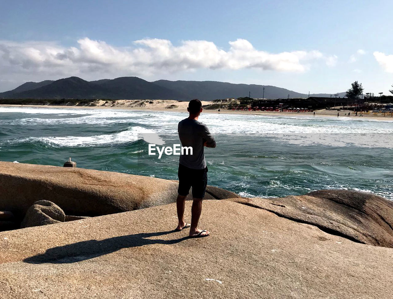 water, sea, one person, standing, real people, sky, lifestyles, leisure activity, full length, scenics - nature, mountain, rock, beach, rock - object, nature, beauty in nature, cloud - sky, solid, outdoors, mountain range, shorts, looking at view