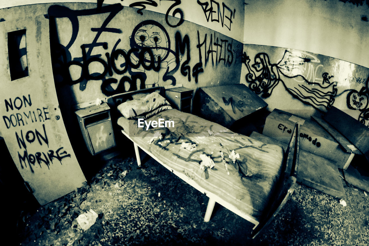graffiti, abandoned, no people, text, indoors, architecture, damaged, communication, day, old, messy, high angle view, decline, western script, destruction, obsolete, bad condition, built structure, dirt, deterioration, ruined