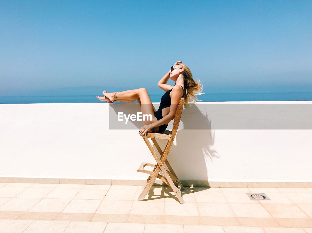 Woman Sitting On Chair In City Against Clear Sky