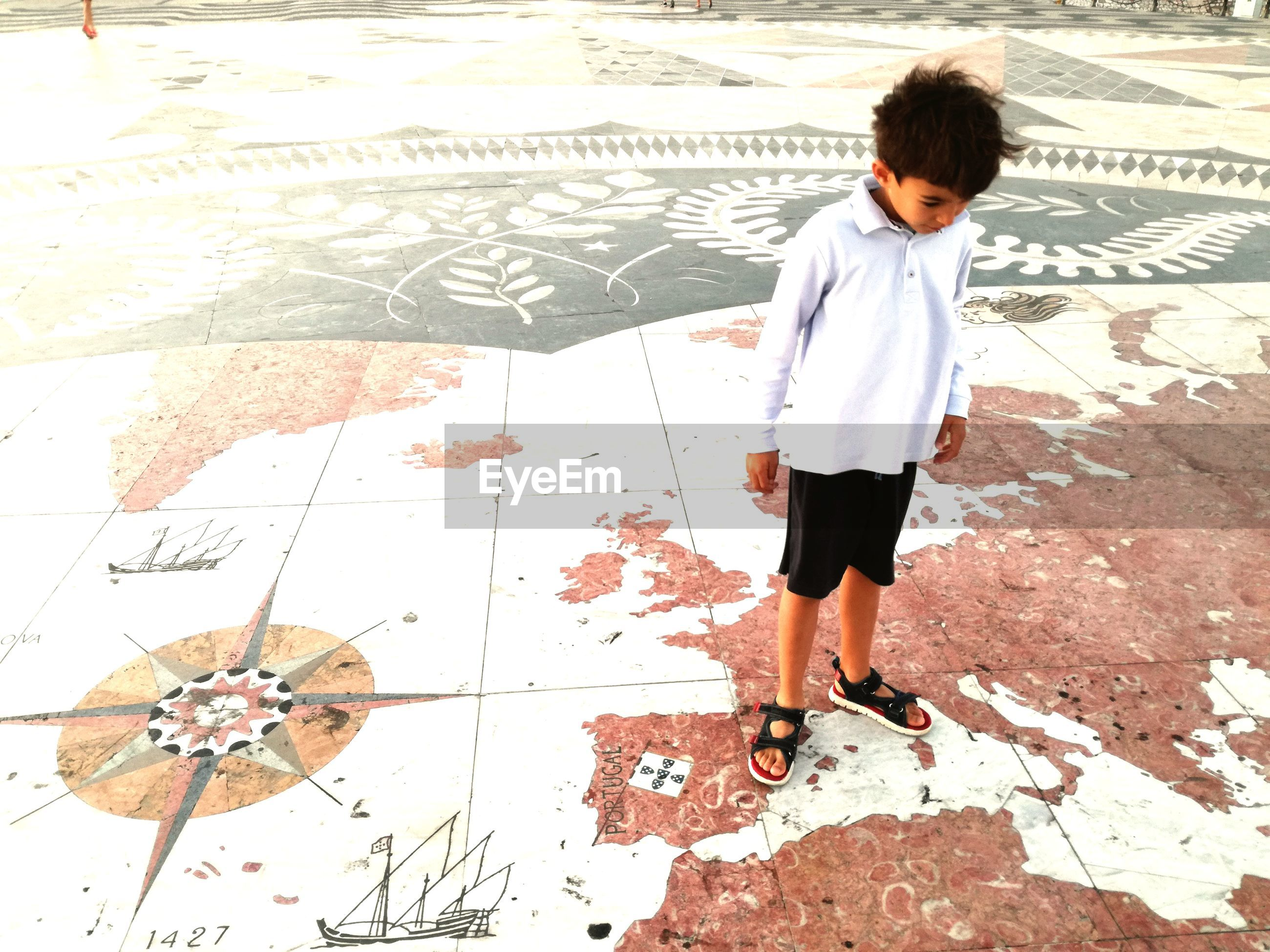 Full length of boy standing on map patterned floor at playground