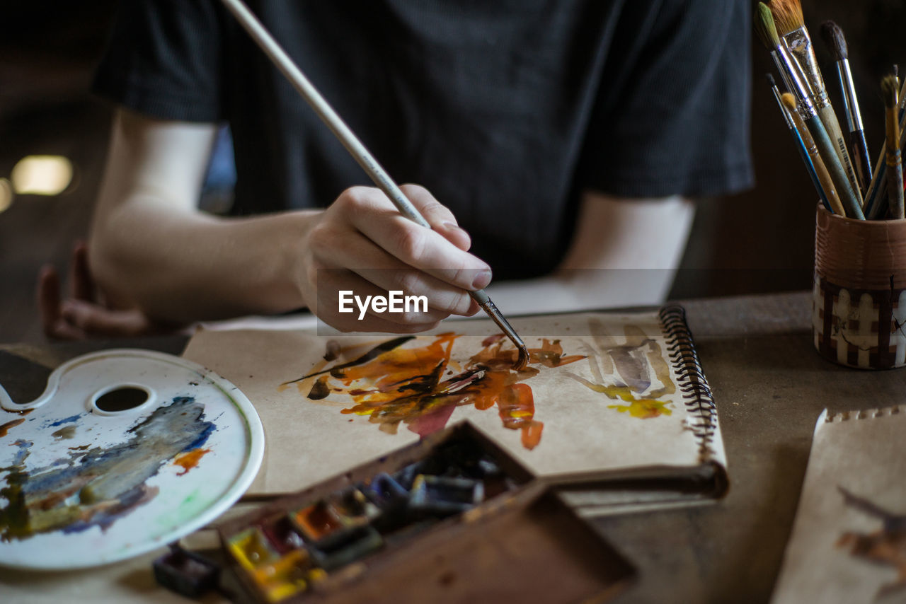 art and craft, creativity, one person, real people, occupation, craft, indoors, selective focus, human hand, holding, skill, table, brush, paintbrush, hand, workshop, artist, human body part, midsection, craftsperson, workbench, watercolor paints, art and craft equipment