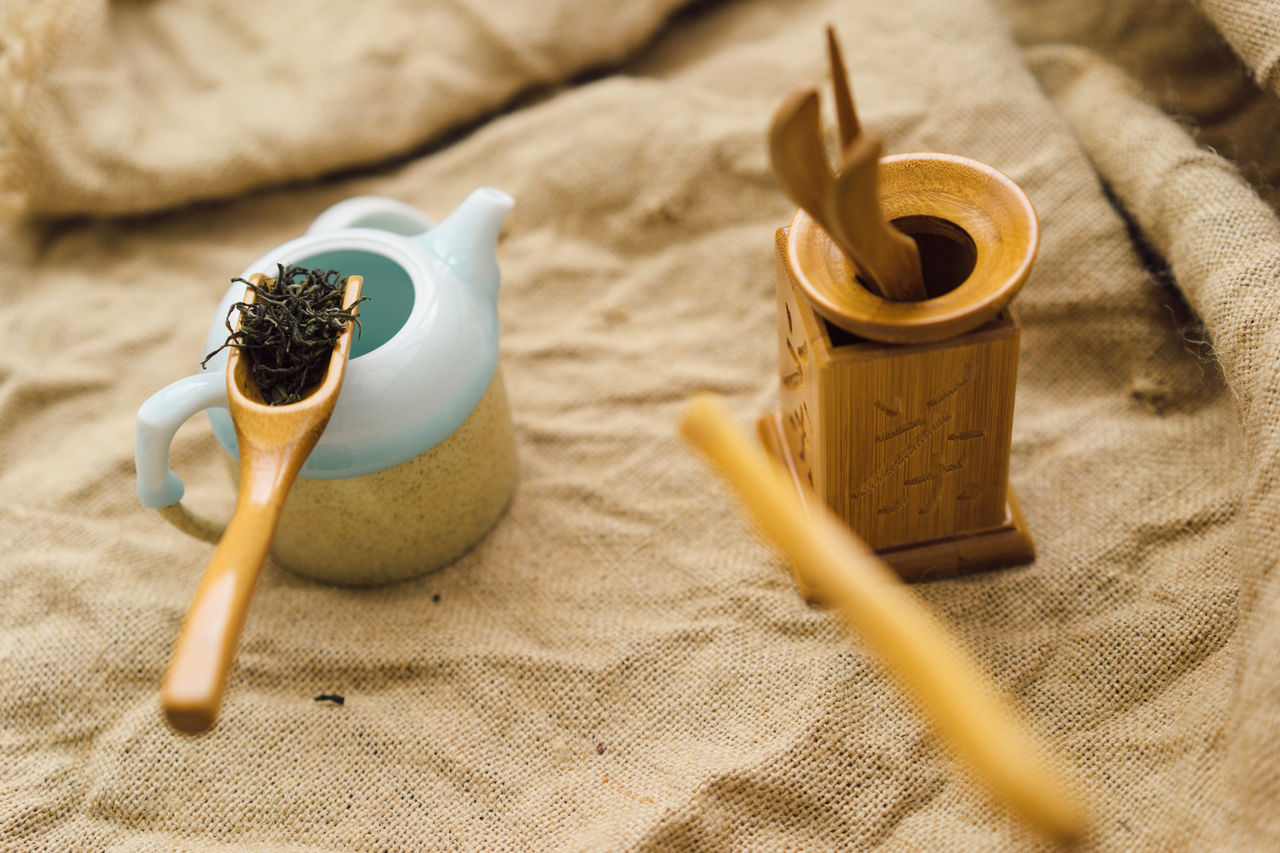 High angle view of tea leaves in spoon with teapot