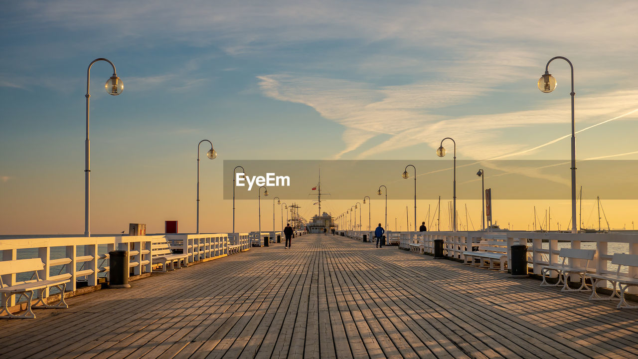 street light, sky, street, the way forward, lighting equipment, cloud - sky, direction, architecture, built structure, sunset, nature, footpath, diminishing perspective, outdoors, city, pier, no people, building exterior, railing, paving stone, long