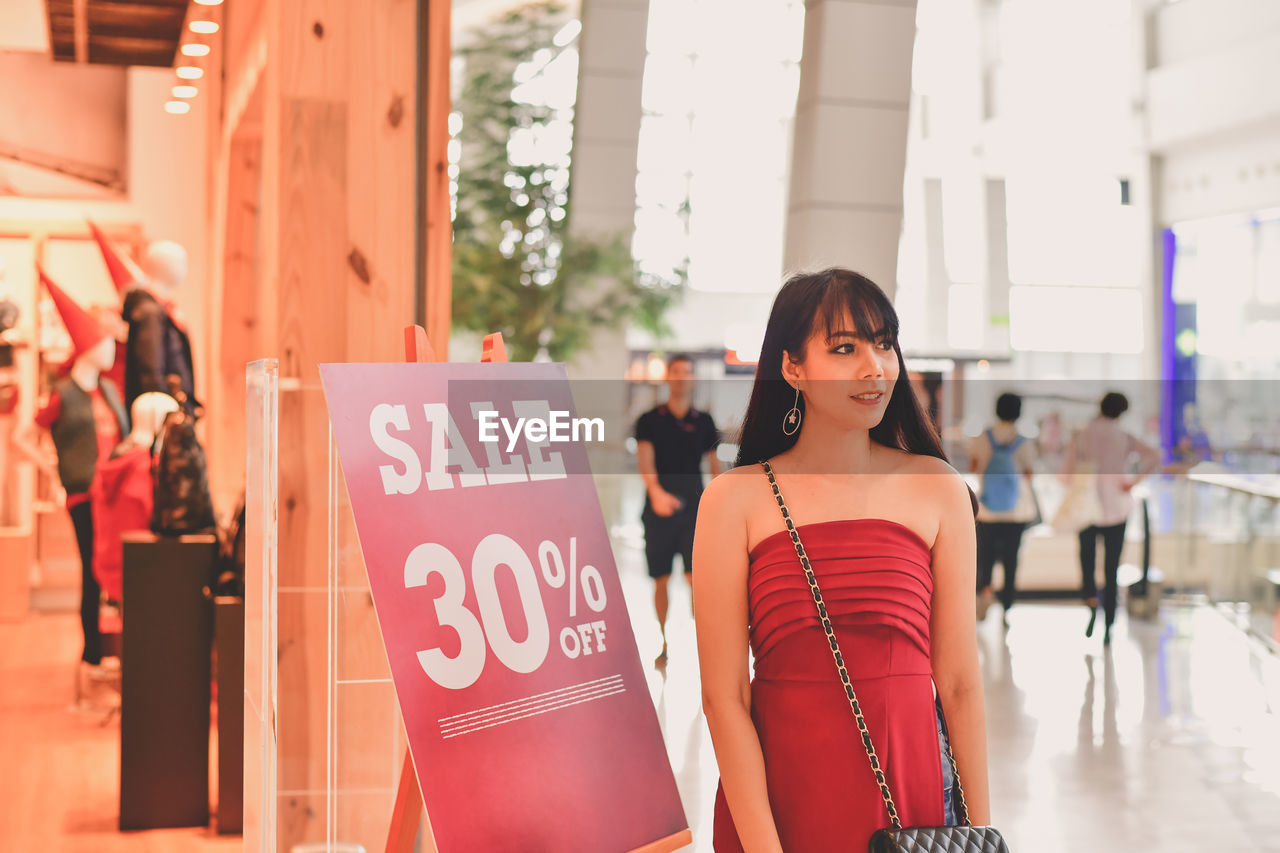 Young Woman Standing By Sign In Shopping Mall