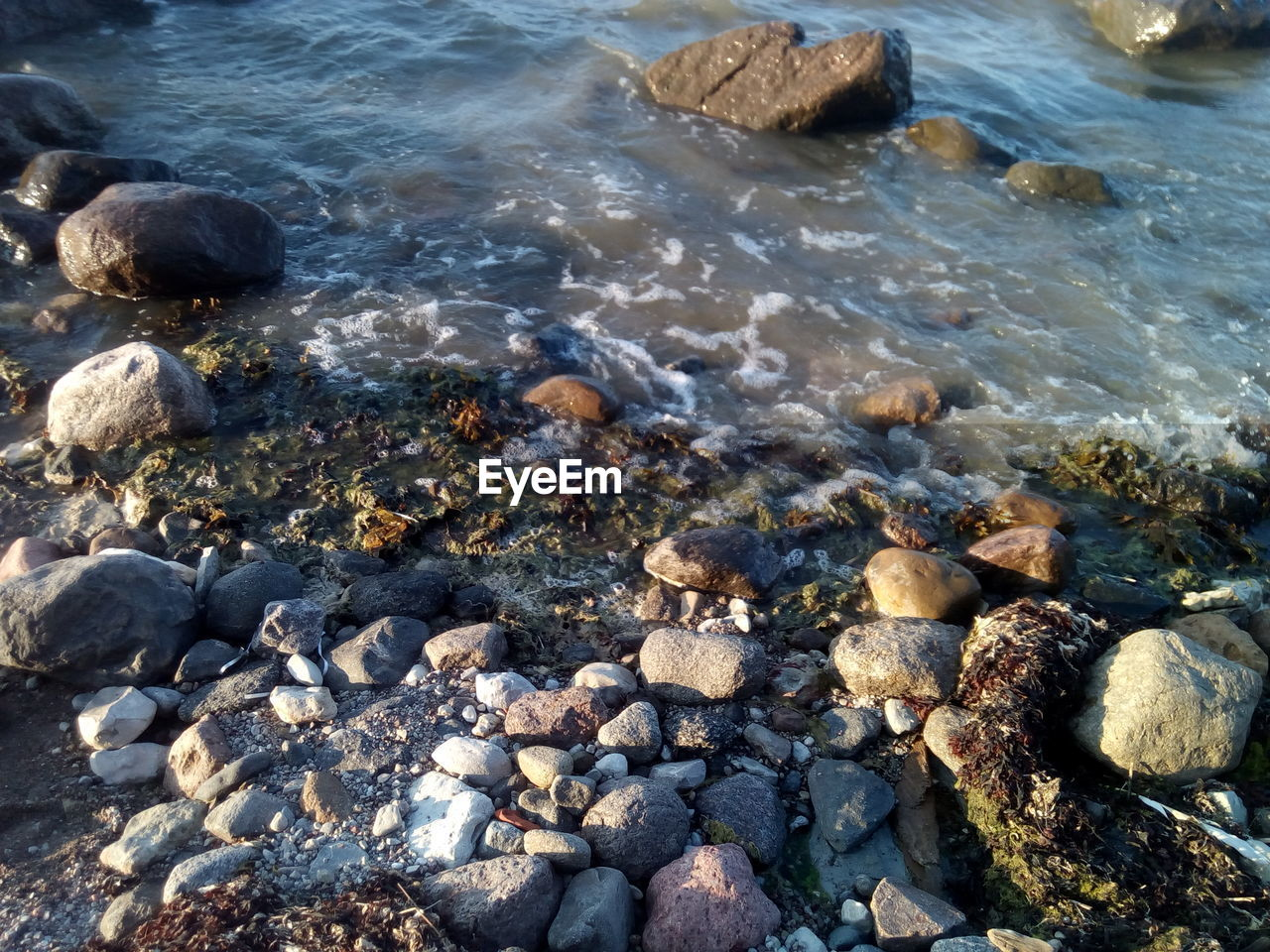 water, rock, solid, beach, sea, land, rock - object, nature, day, stone - object, stone, motion, pebble, high angle view, beauty in nature, aquatic sport, outdoors, sport, wave, flowing, flowing water, shallow, clean