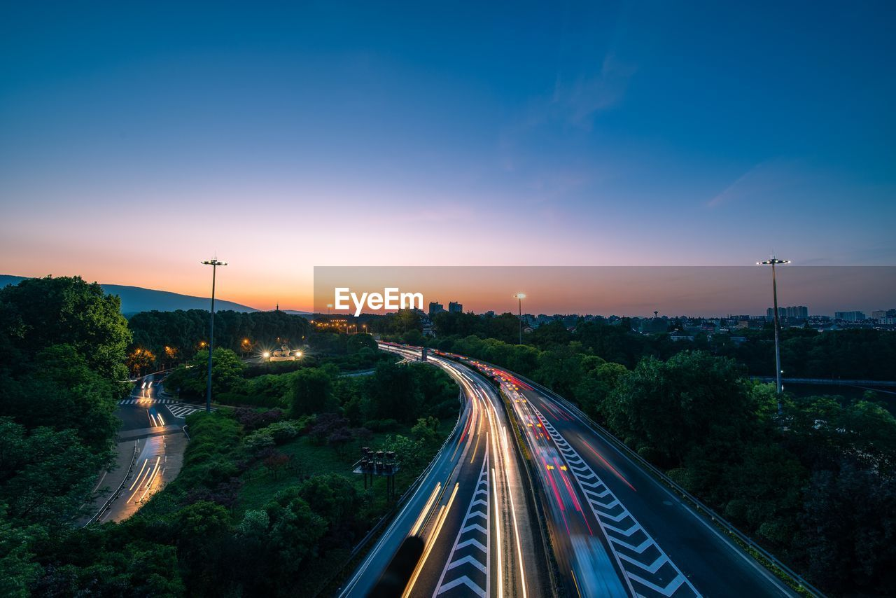 High Angle View Of Light Trails On Road At Sunset