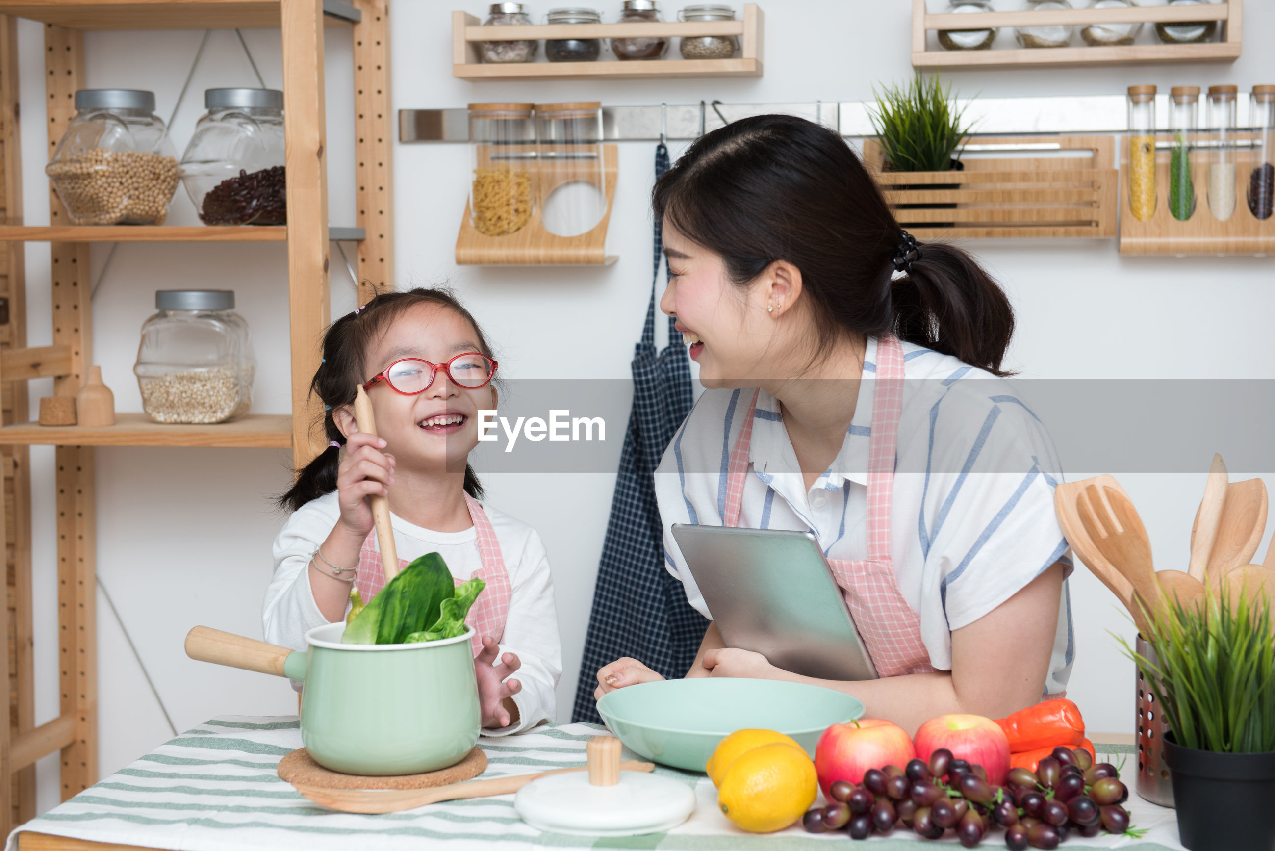 Cheerful mother and daughter preparing food in kitchen