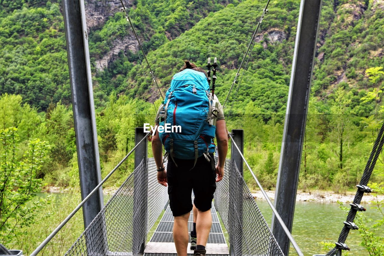 rear view, tree, plant, bridge, walking, forest, real people, one person, day, nature, full length, bridge - man made structure, leisure activity, railing, rope, land, lifestyles, rope bridge, green color, footbridge, outdoors