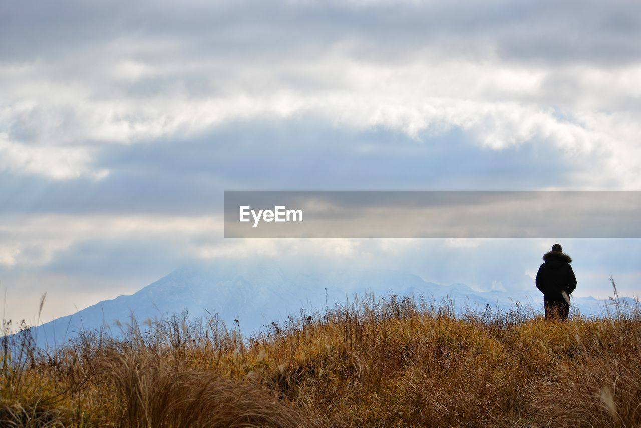 cloud - sky, real people, sky, rear view, beauty in nature, one person, men, lifestyles, mountain, scenics - nature, land, nature, non-urban scene, tranquil scene, leisure activity, tranquility, standing, plant, day, outdoors, looking at view