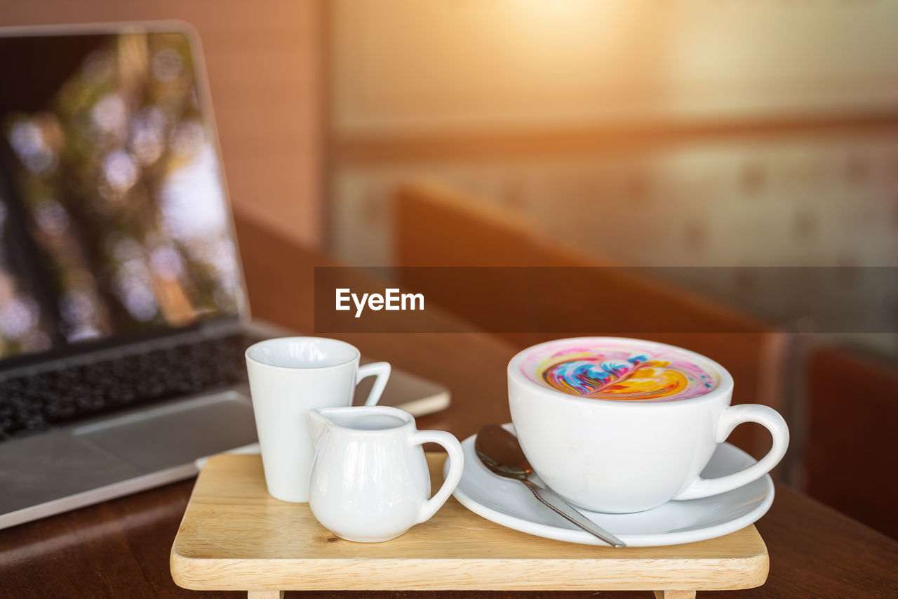 High angle view of coffee cup with laptop on wooden table