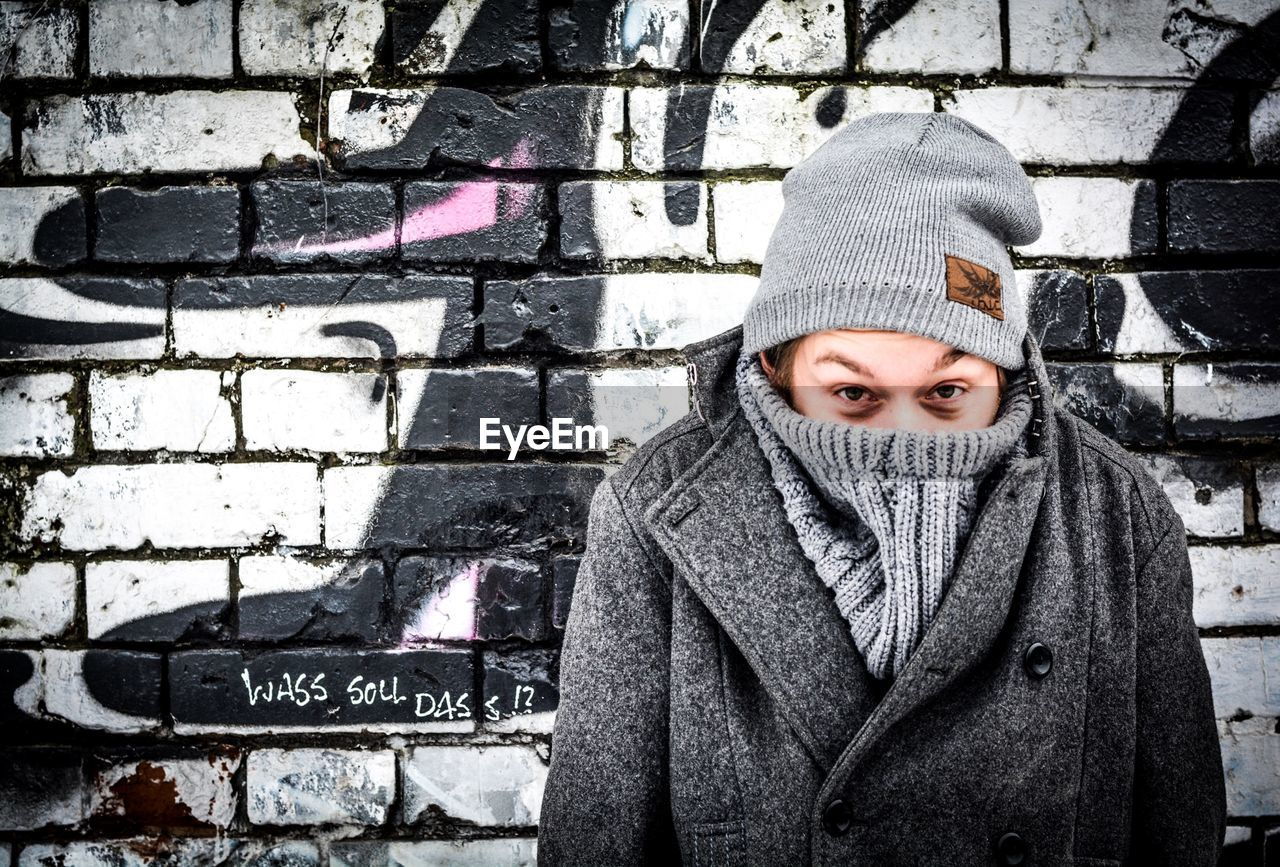 Portrait Of Man Covering Face With Warm Clothing While Standing Against Wall
