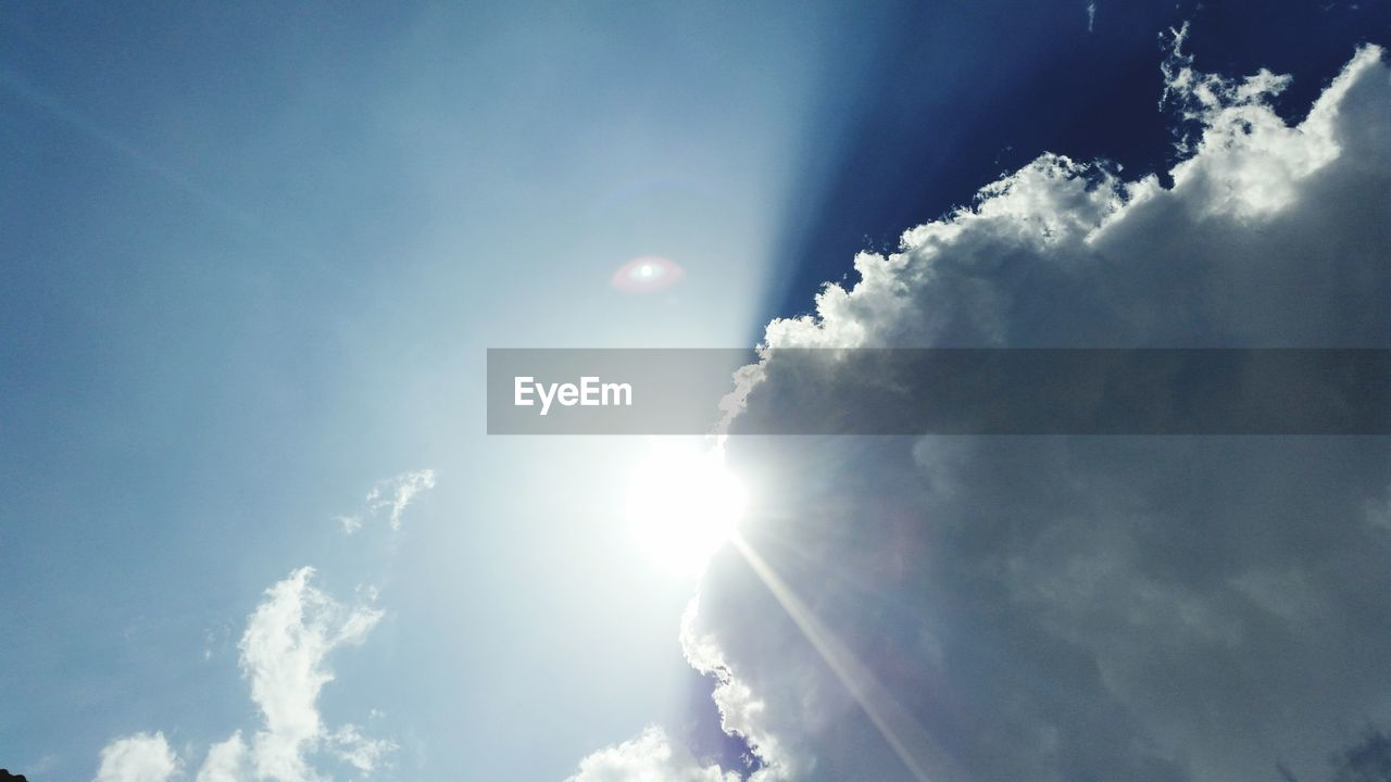 Sun shining through clouds in sky