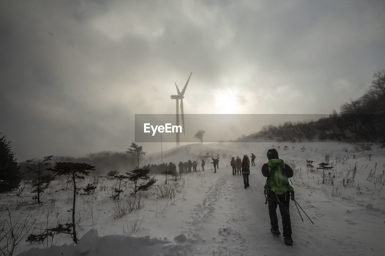snow, sky, cold temperature, winter, rear view, fuel and power generation, turbine, real people, beauty in nature, wind turbine, environment, alternative energy, one person, cloud - sky, environmental conservation, lifestyles, nature, renewable energy, wind power, outdoors, warm clothing