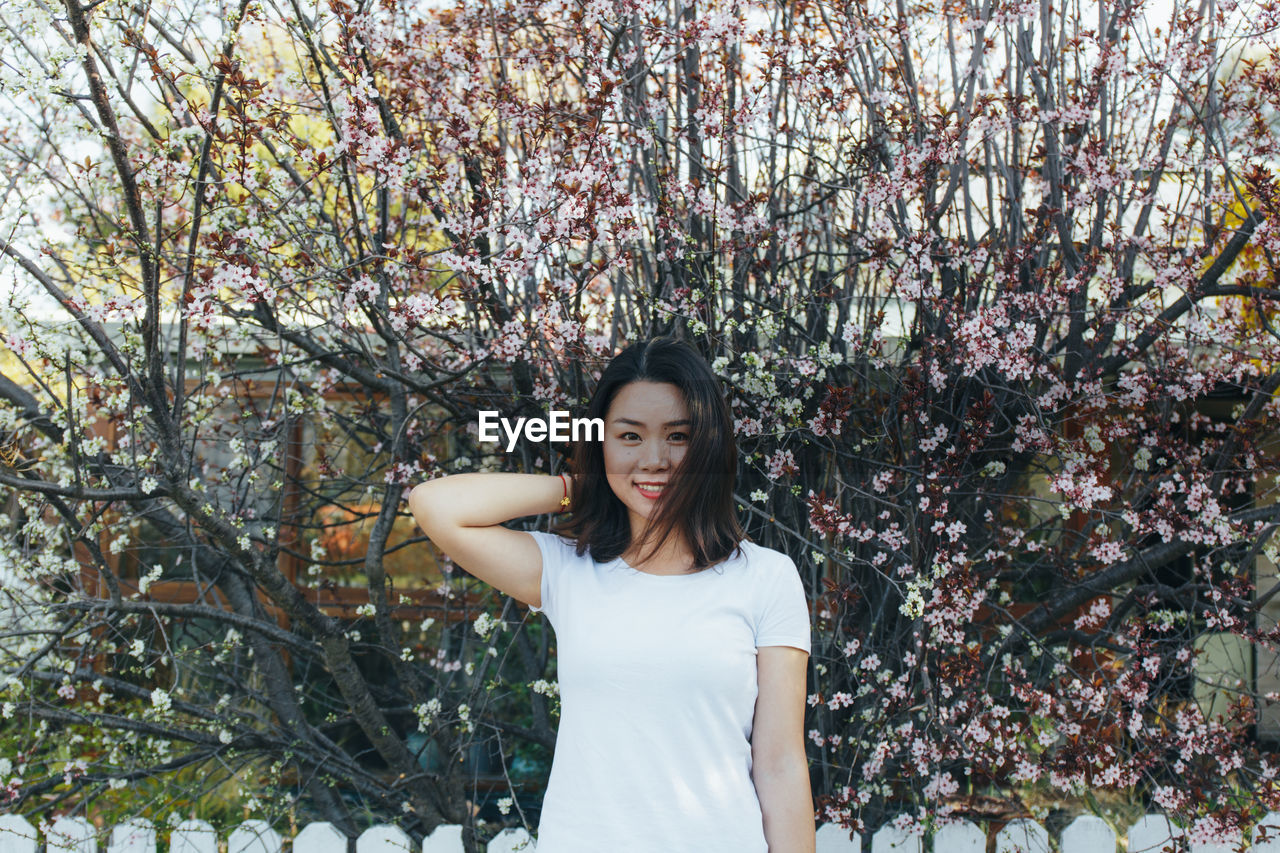 tree, plant, young women, one person, leisure activity, standing, real people, young adult, lifestyles, casual clothing, hair, women, front view, hairstyle, long hair, portrait, nature, flowering plant, beauty in nature, beautiful woman, springtime, outdoors, cherry blossom