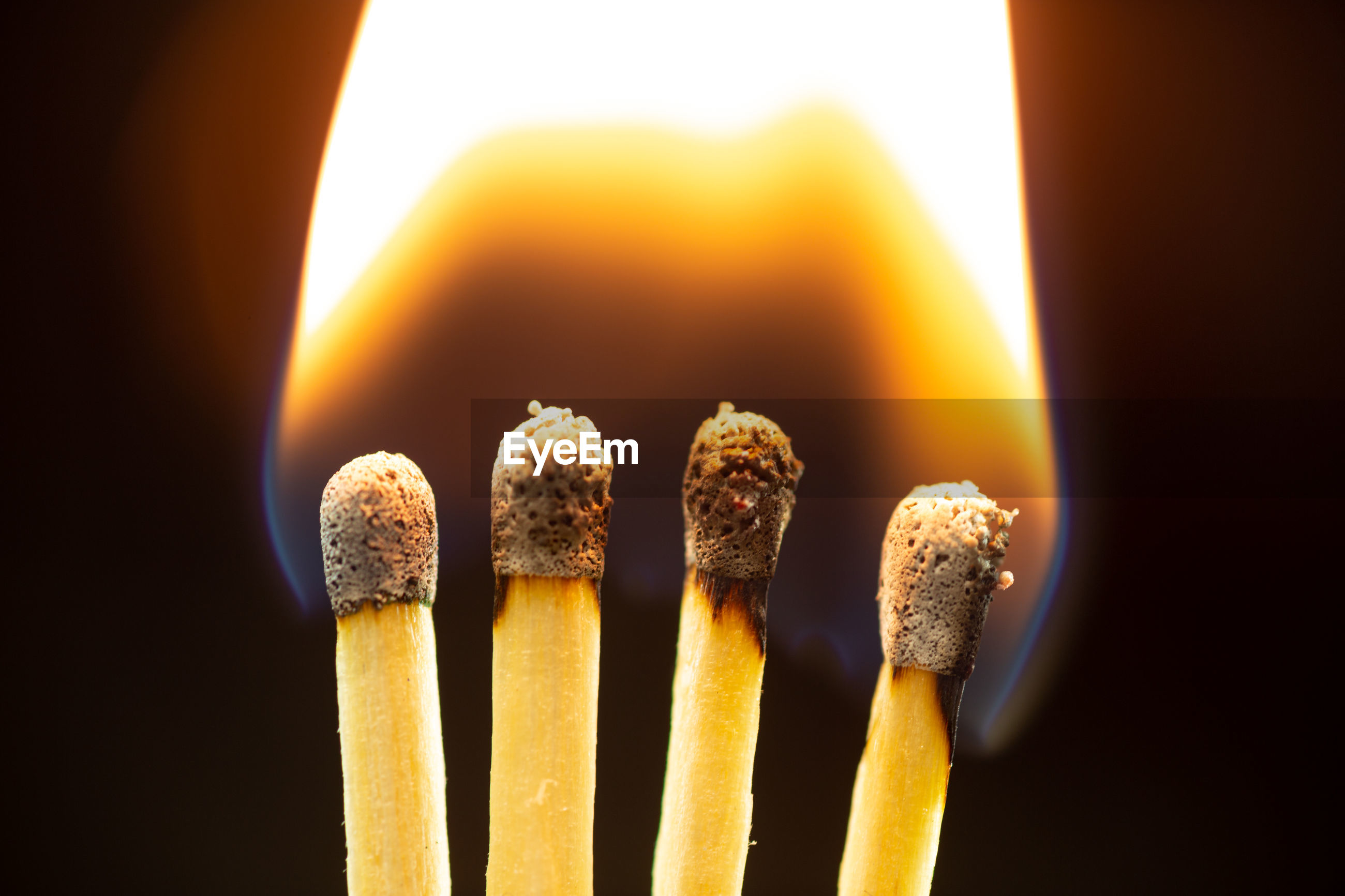 CLOSE-UP OF BURNING CANDLES ON WOOD AGAINST BLACK BACKGROUND