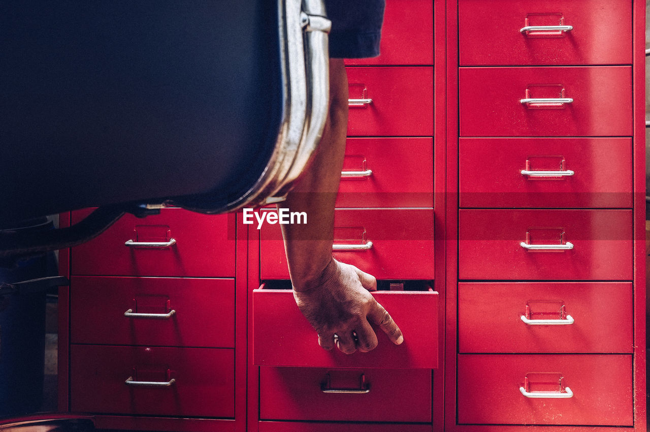 Low section of person opening drawer