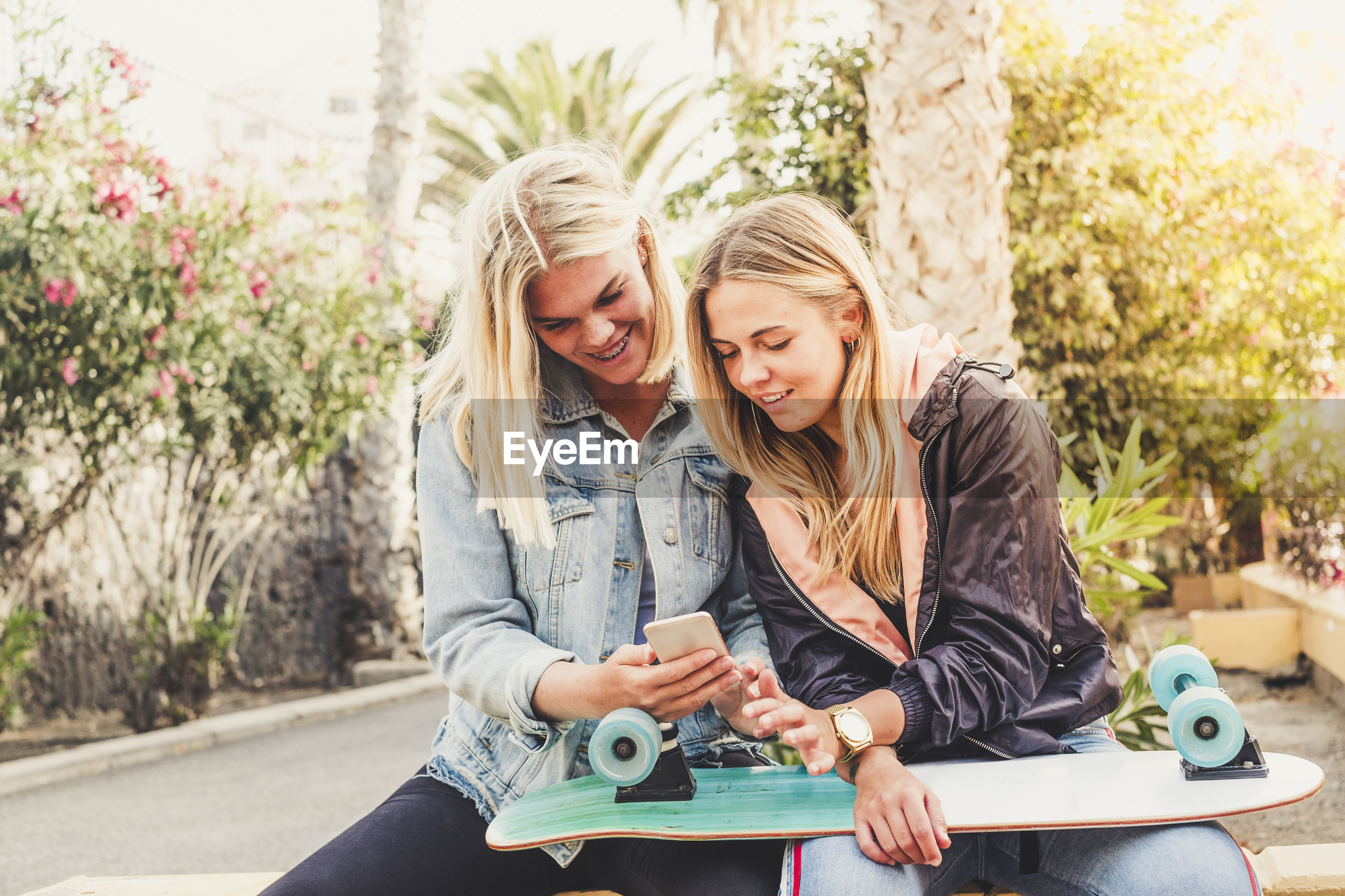 Smiling friends using smart phone while sitting in park