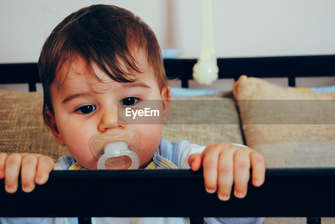 Portrait of cute baby girl sucking pacifier in crib