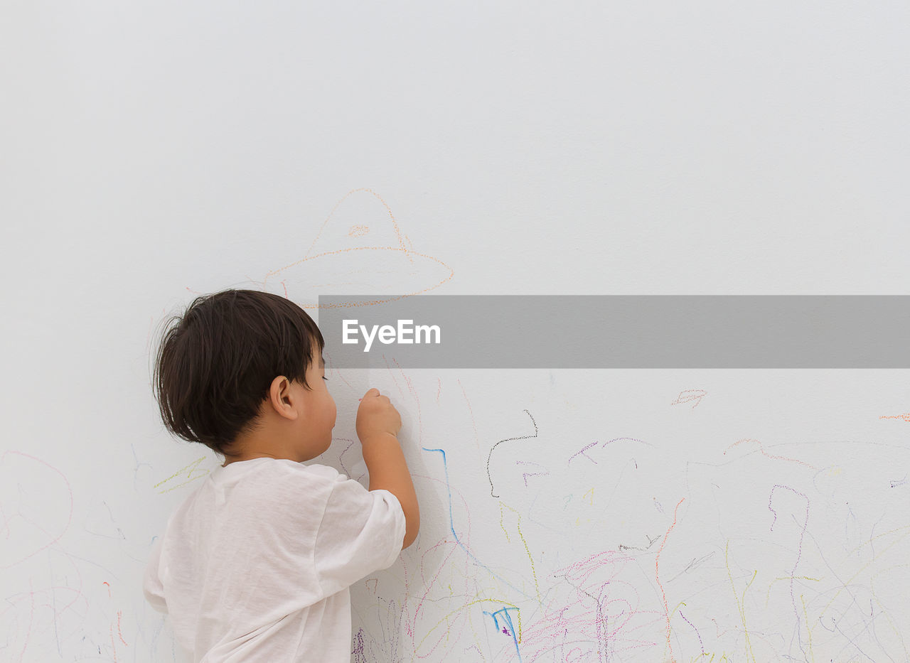 Rear view of boy writing on wall