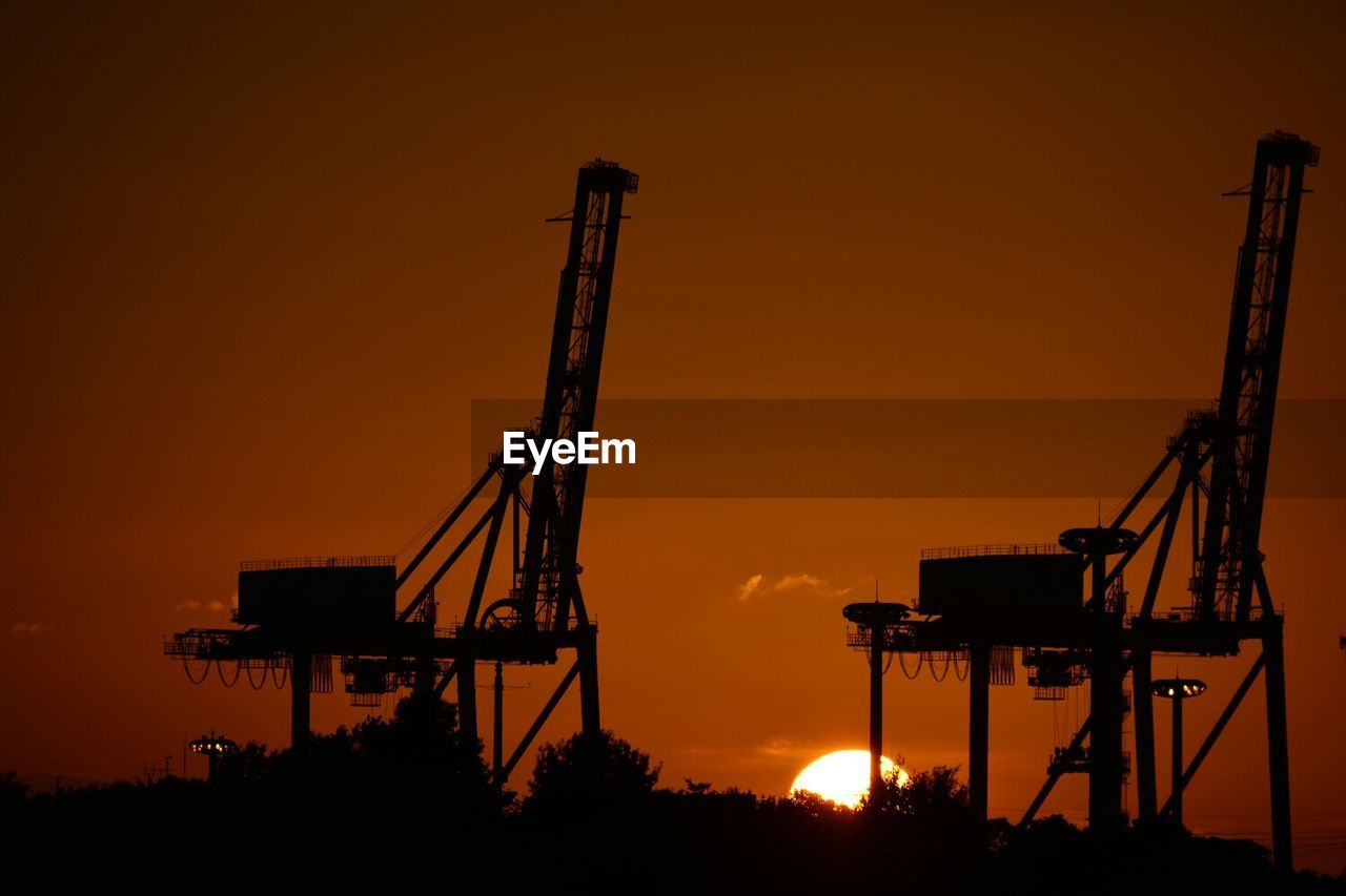 Silhouette Cranes At Sunset