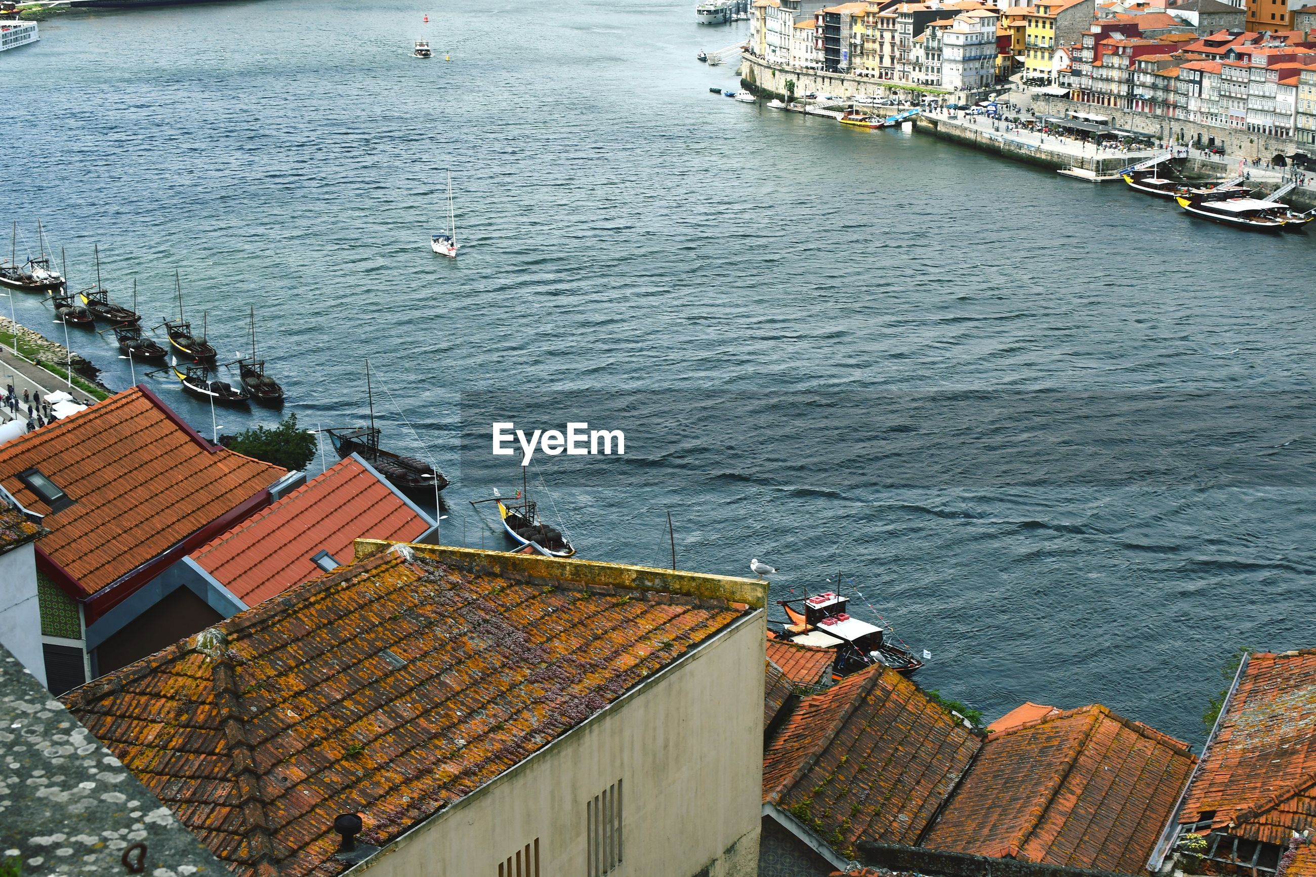 HIGH ANGLE VIEW OF TOWNSCAPE BY SEA AGAINST BUILDINGS