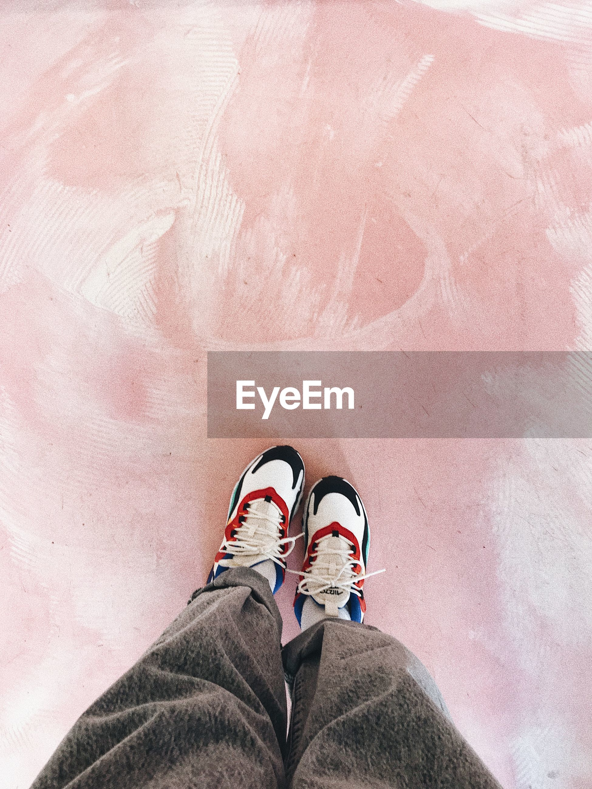 LOW SECTION VIEW OF PERSON STANDING ON PINK SHOES