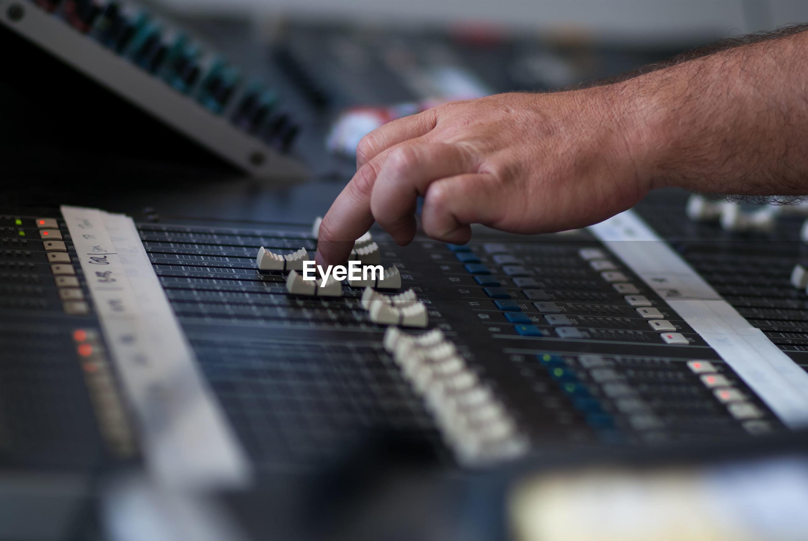 Technician adjusting sound mixer at studio
