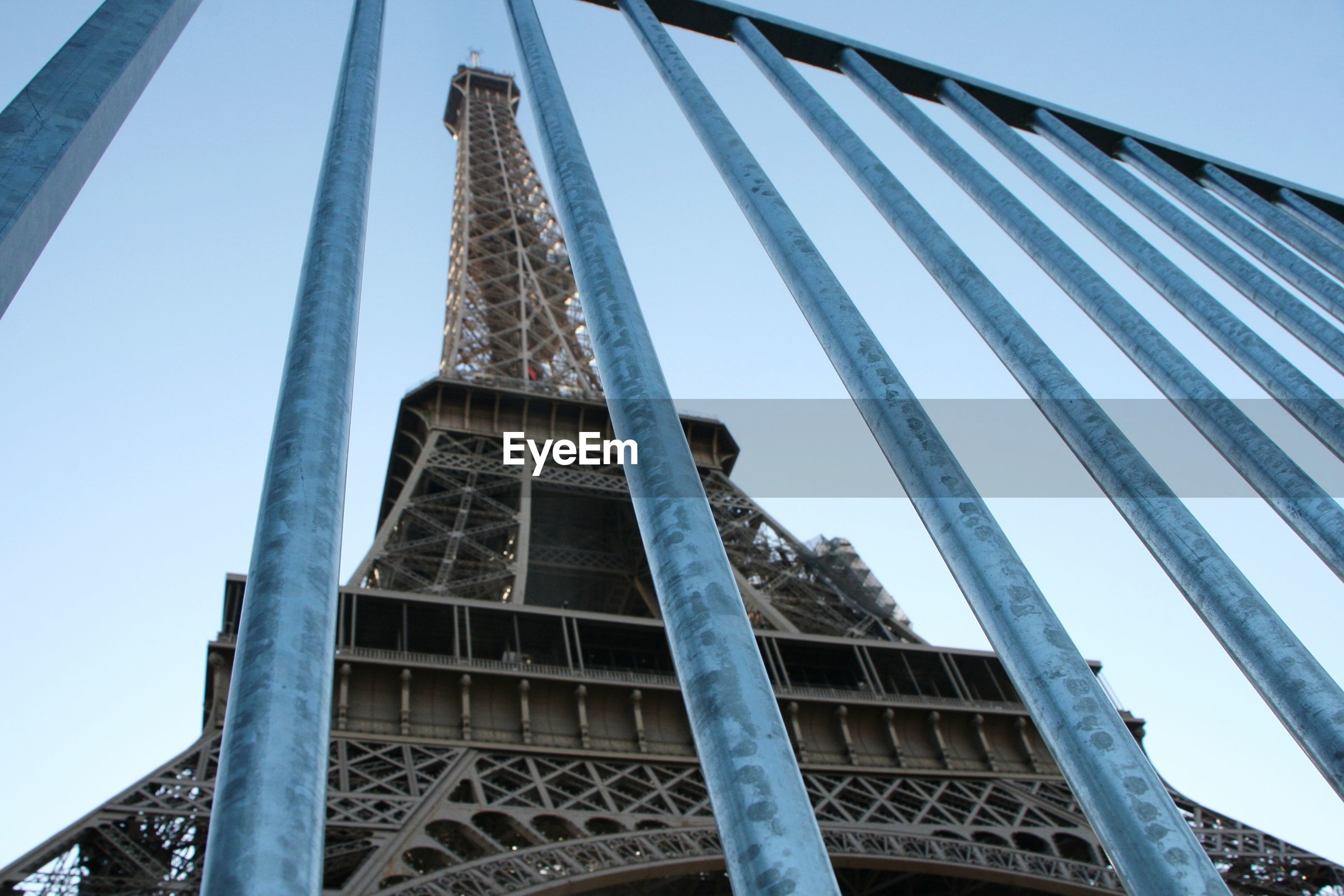 Low angle view of eiffel tower seen through railing against sky