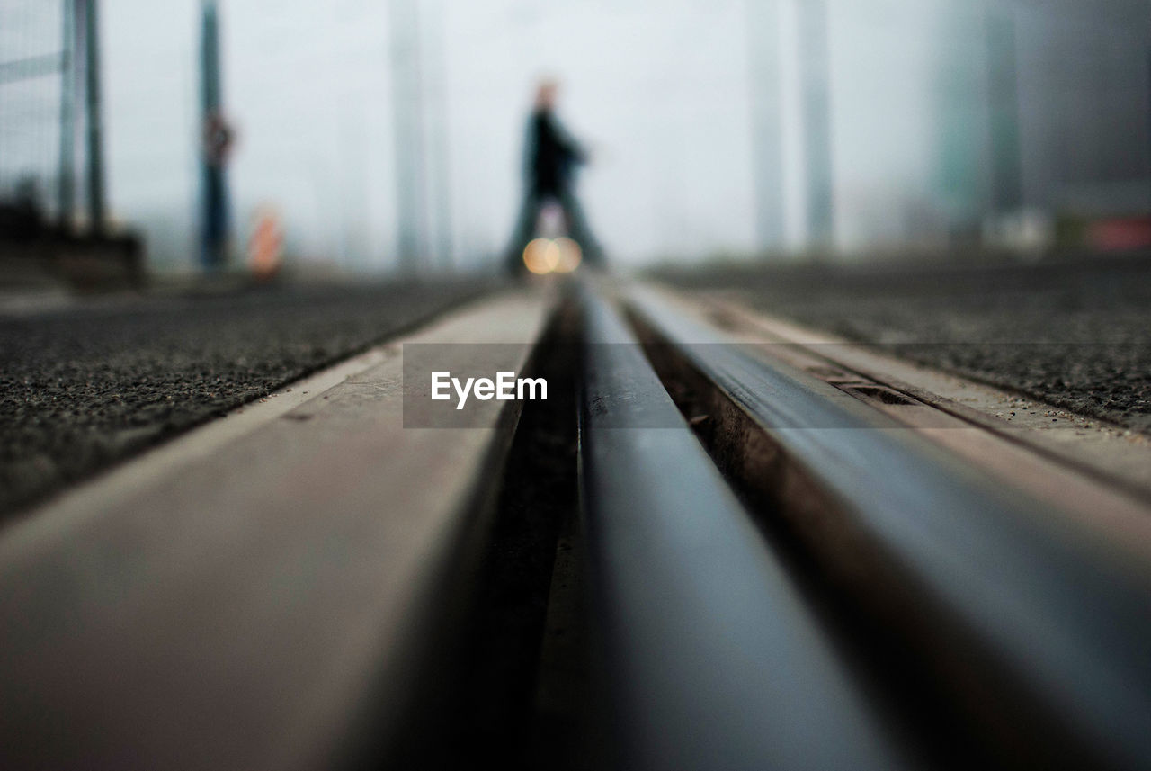 Surface Level Of Railroad Track With Person Walking In Background