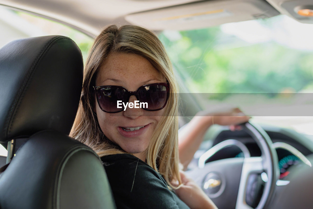 Portrait of smiling young woman wearing sunglasses in car