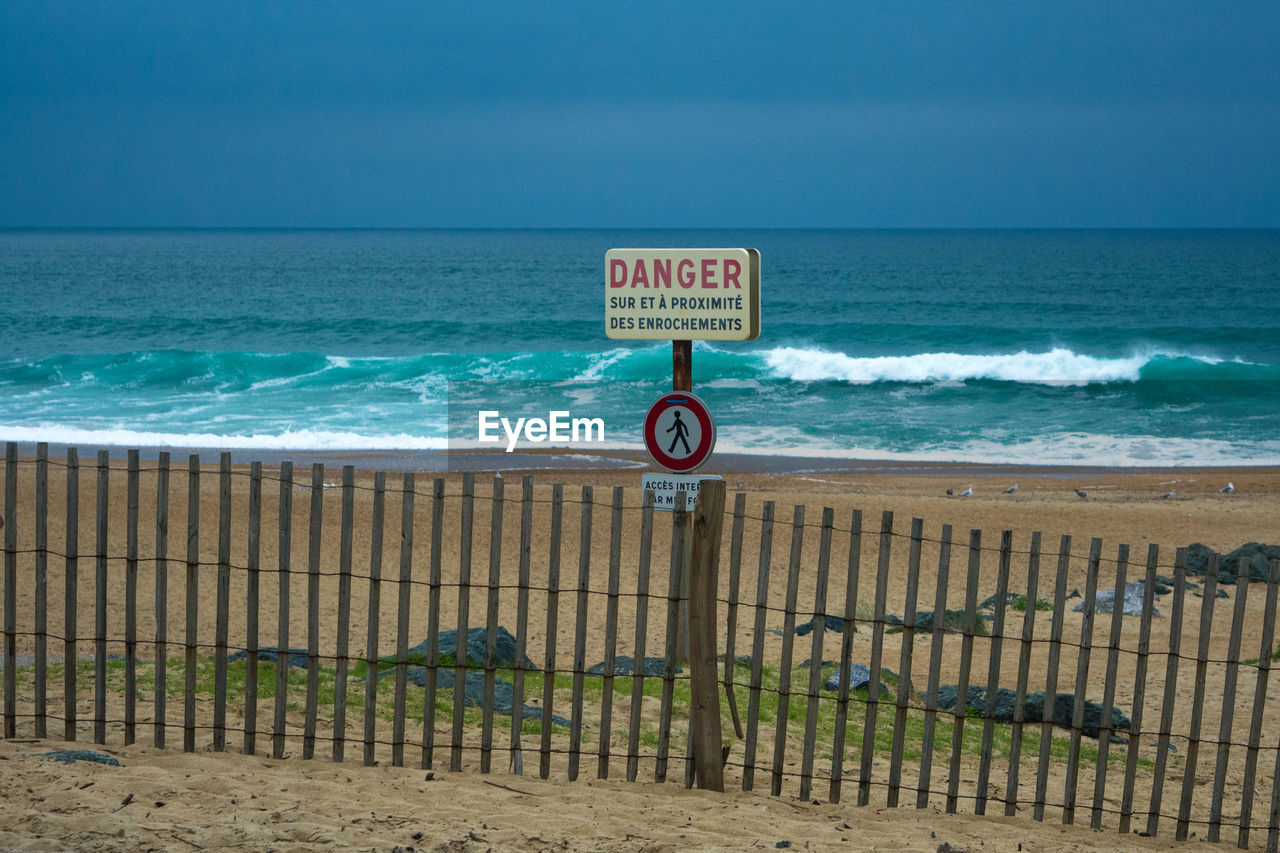 Danger sign on fence at beach