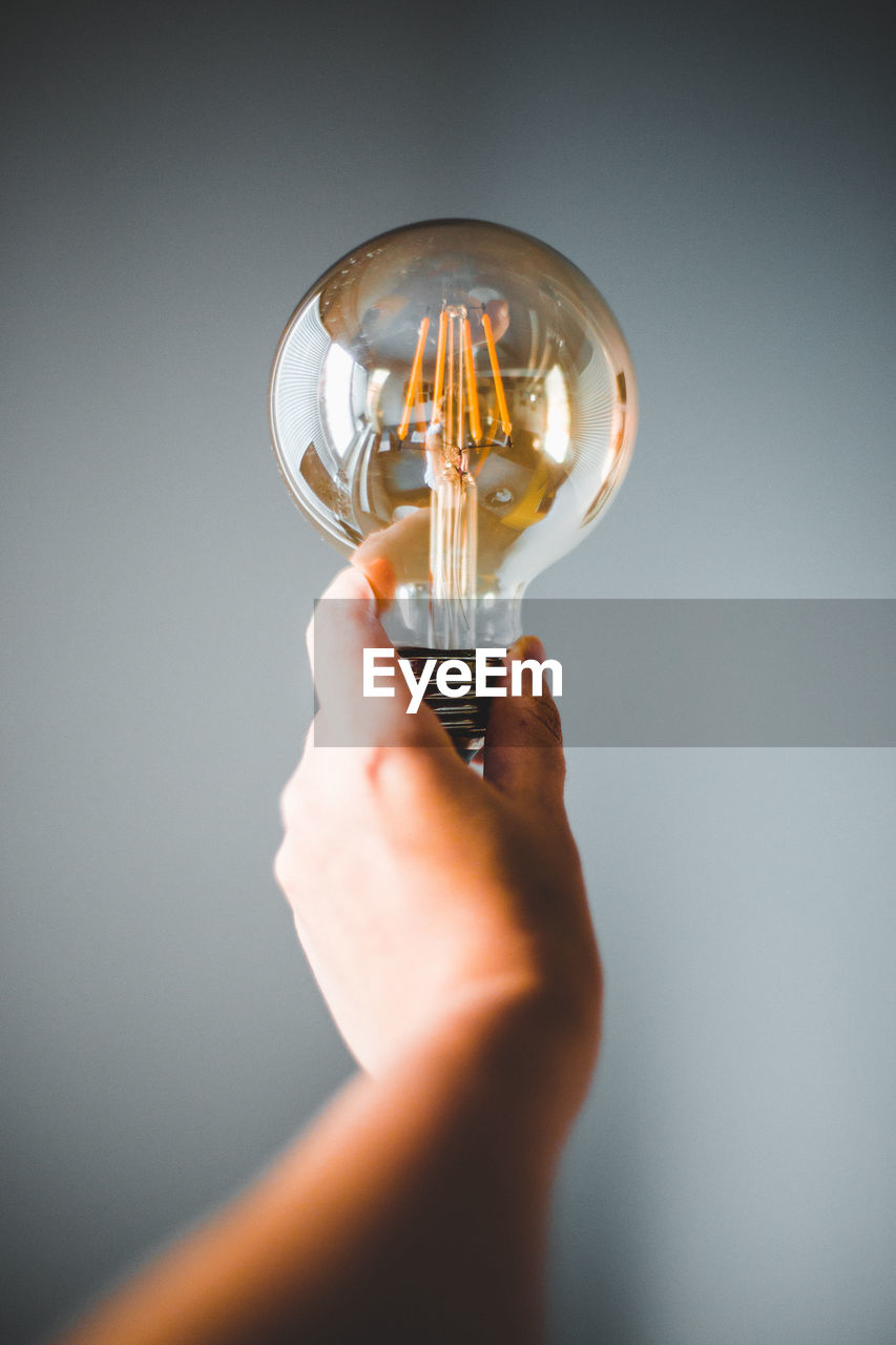 Close-up of hand holding light bulb against gray background