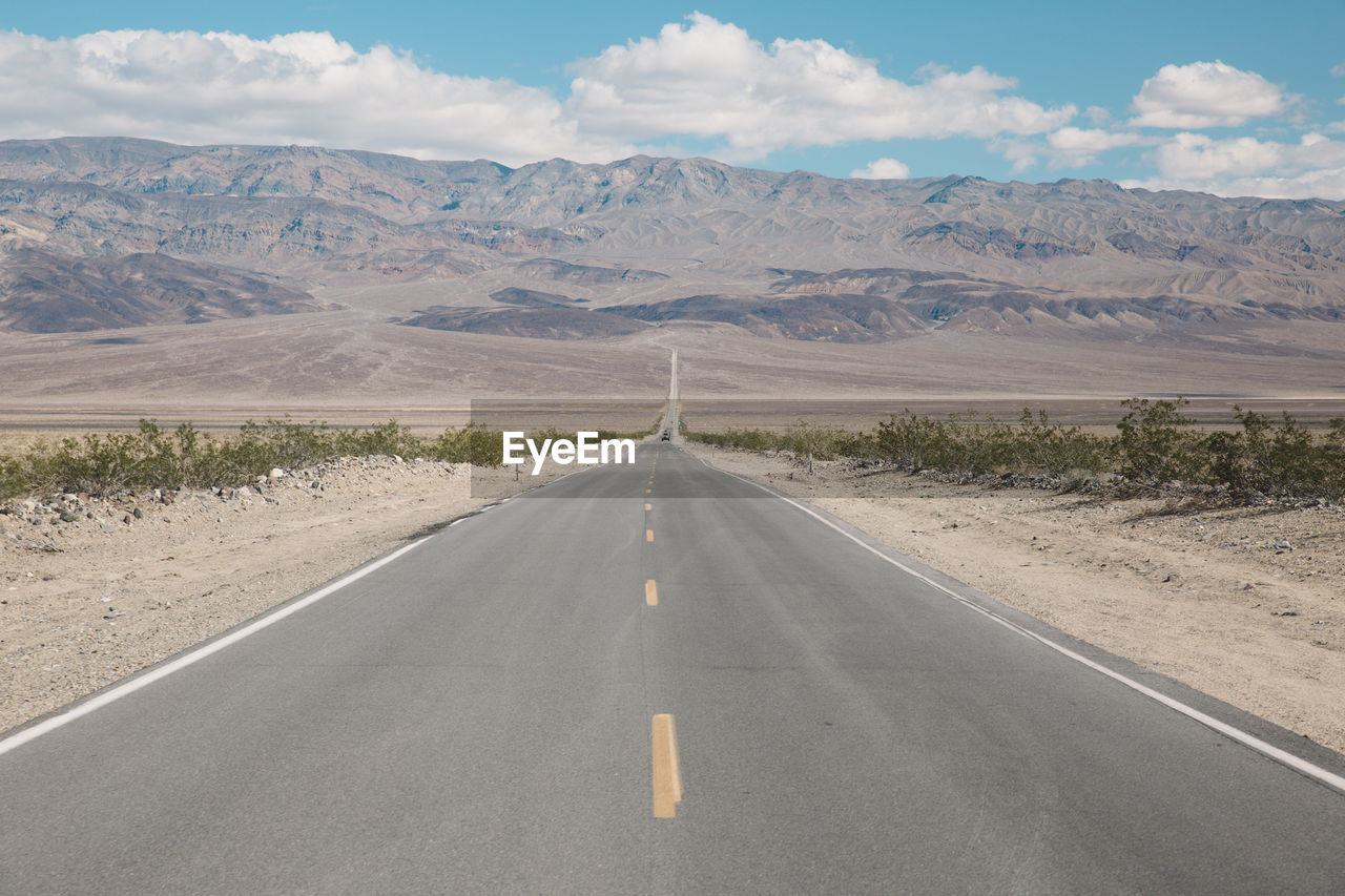 Empty road amidst field leading towards mountains
