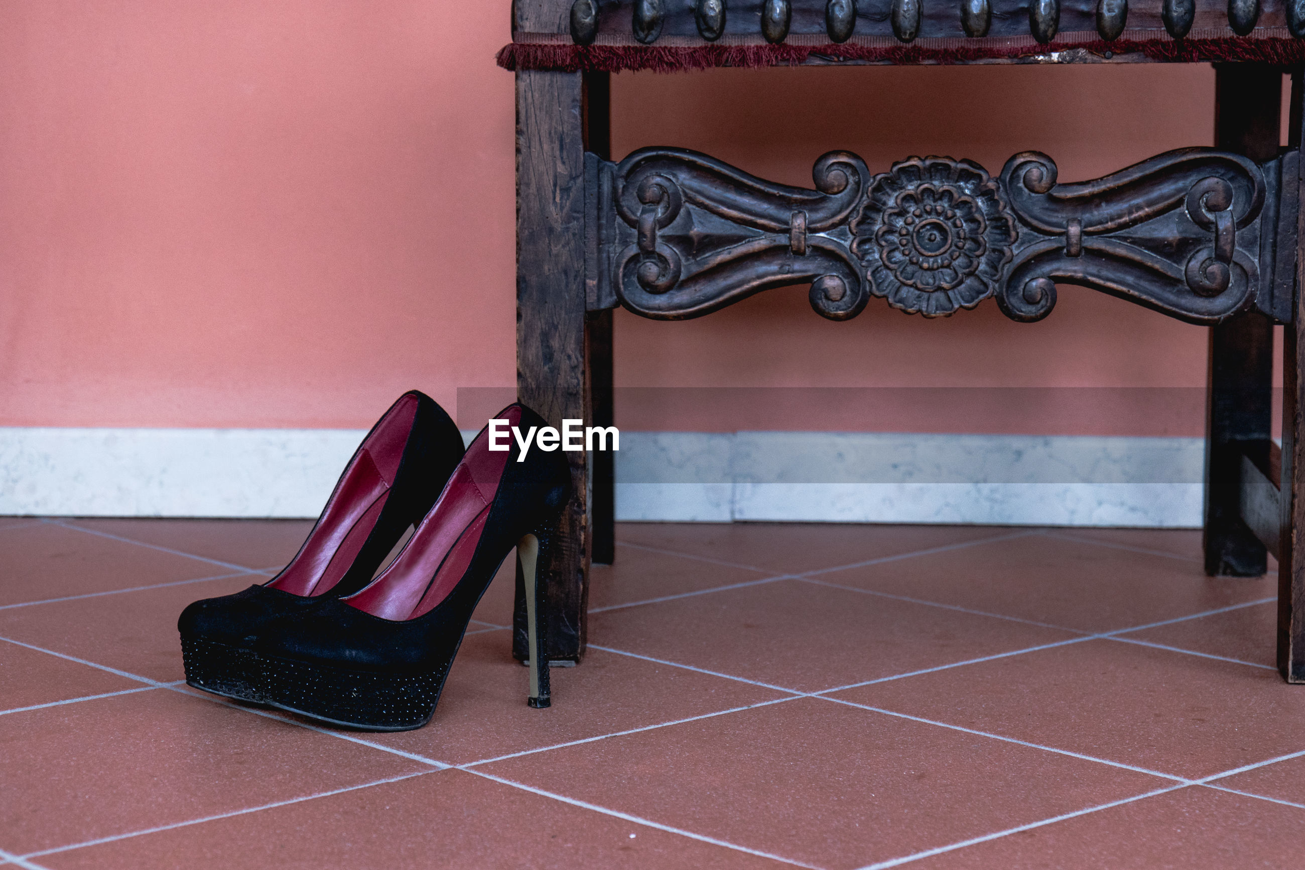 Close-up of empty shoes on tiled floor against wall