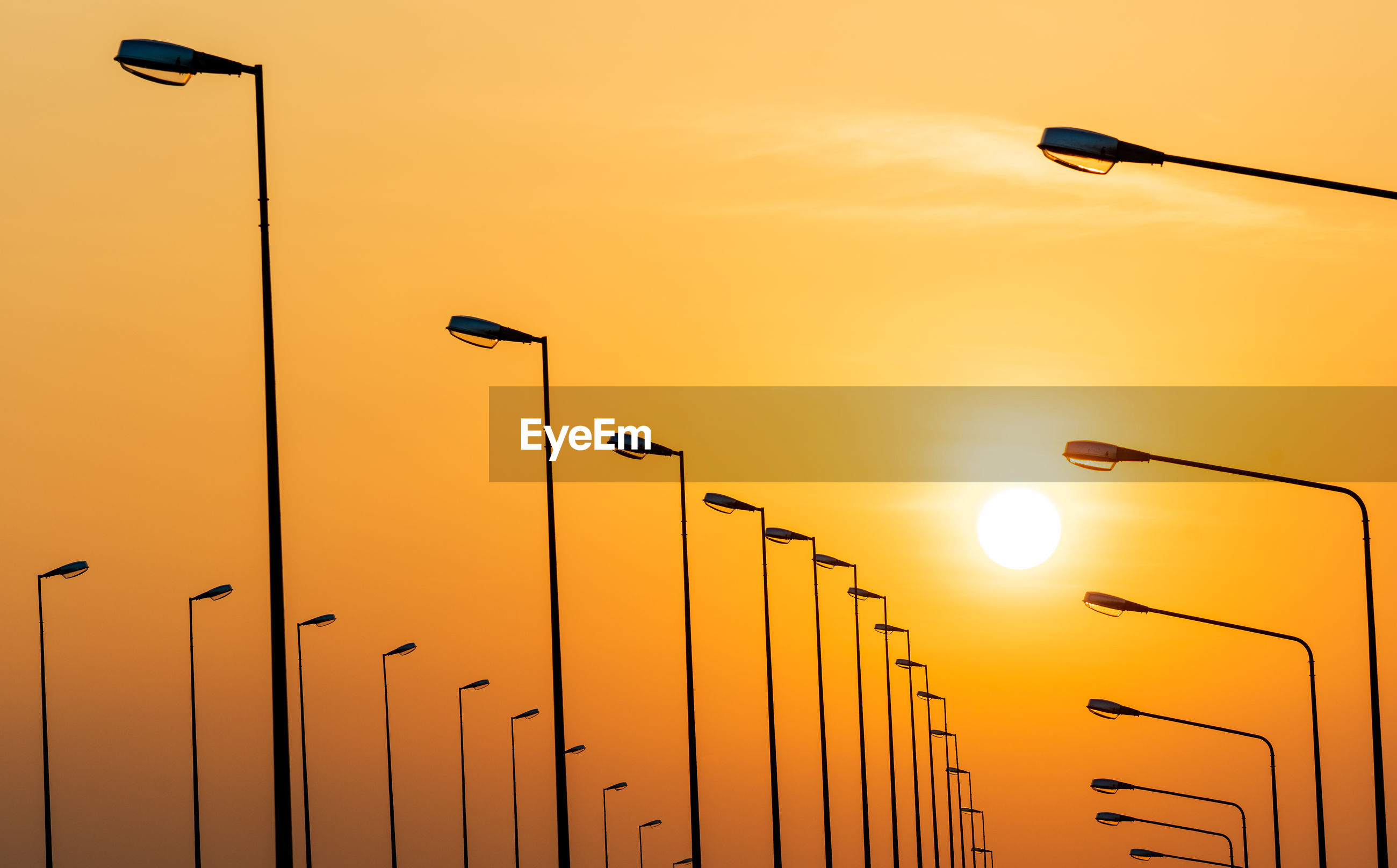 LOW ANGLE VIEW OF STREET LIGHT AGAINST ORANGE SKY