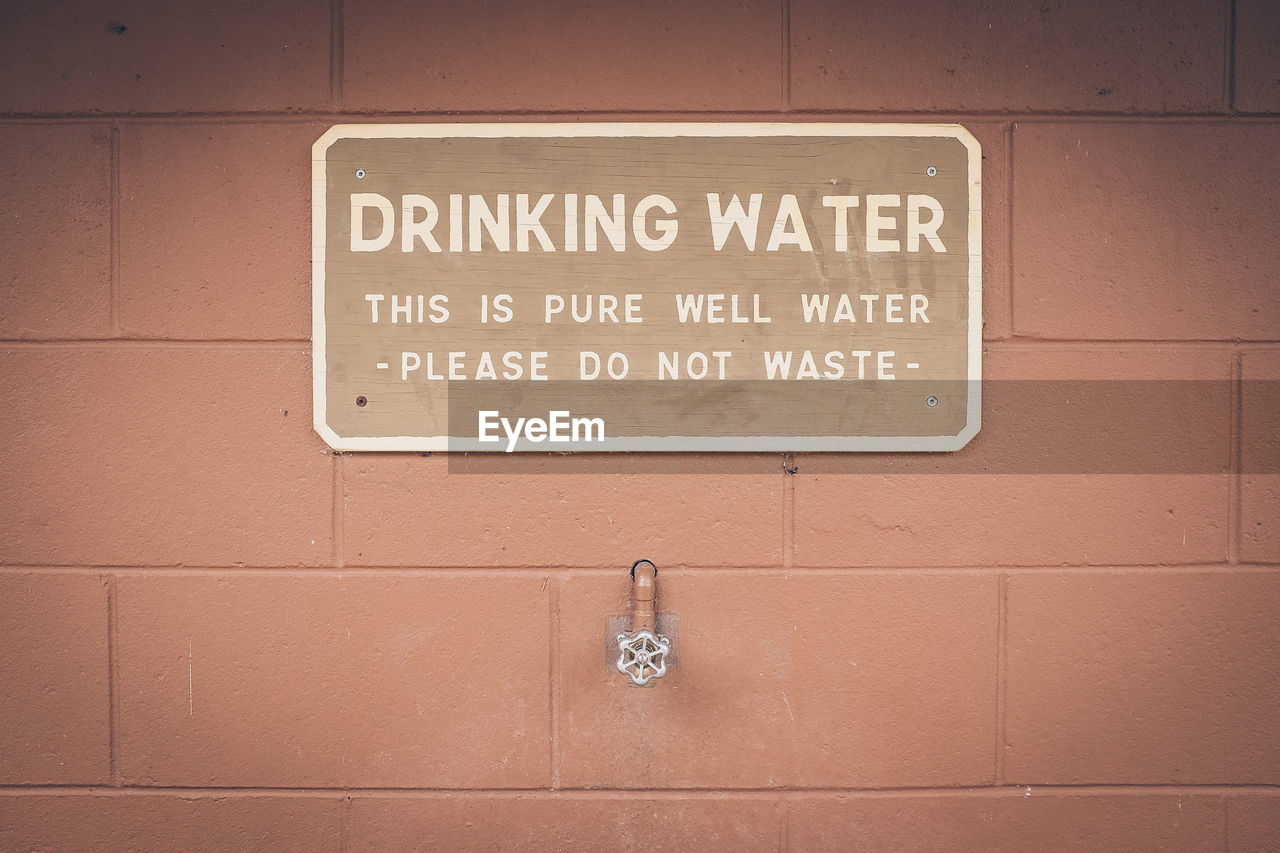 Text On Placard With Valve Against Concrete Wall