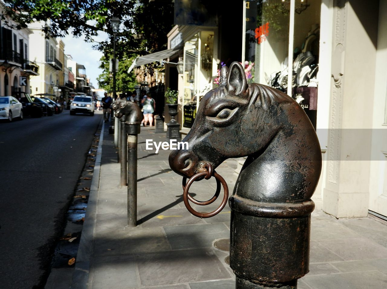 city, sculpture, incidental people, art and craft, architecture, statue, street, mammal, creativity, built structure, building exterior, representation, animal representation, sidewalk, animal, day, footpath, animal themes, craft, outdoors