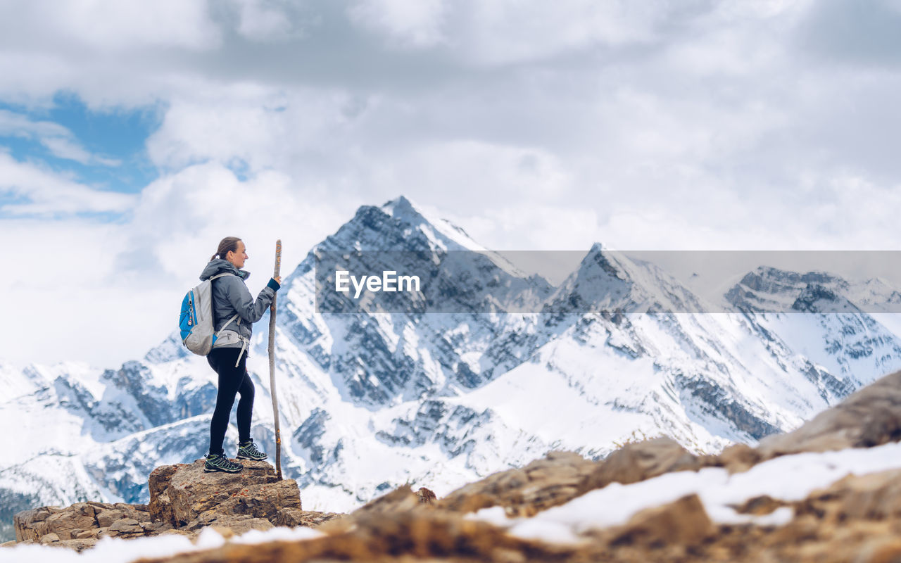 Side View Of Mid Adult Woman Standing On Snowcapped Mountain Against Sky