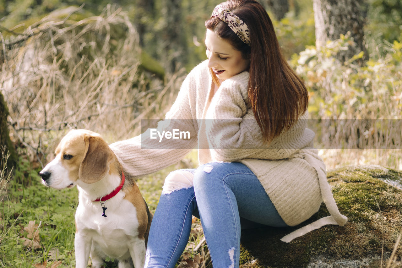YOUNG WOMAN WITH DOG SITTING ON GRASS