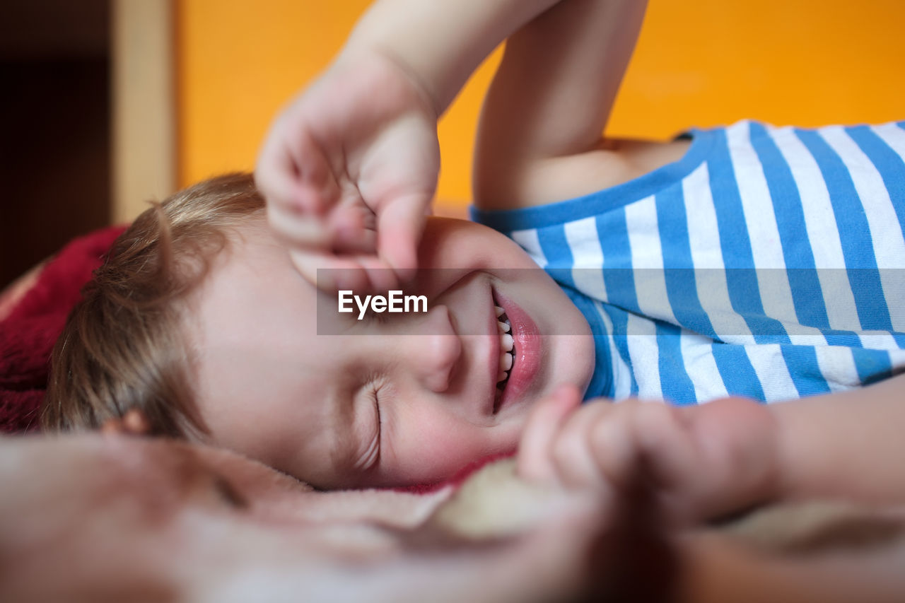 Close-Up Of Boy Rubbing Eyes While Lying On Bed