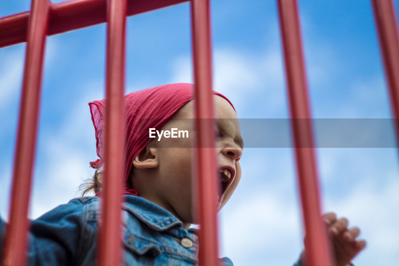 Cut Boy Screaming Seen Through Railing Against Sky