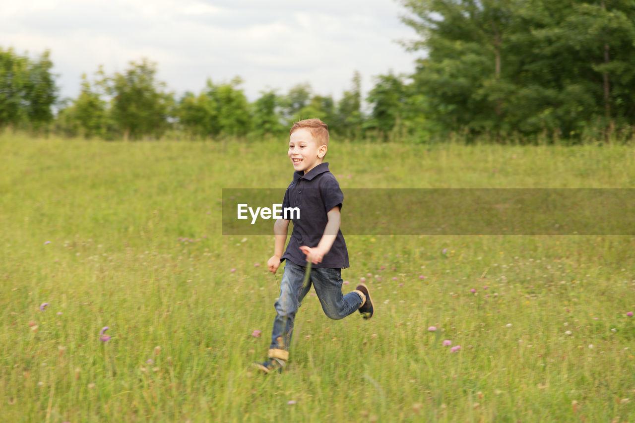 Full Length Of Smiling Boy Running On Field