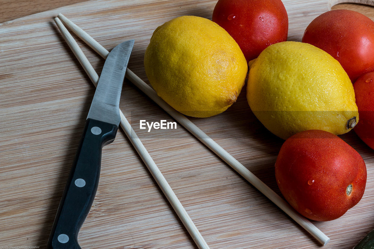 Close-Up Of Tomatoes And Lemons With Kitchen Knife On Table