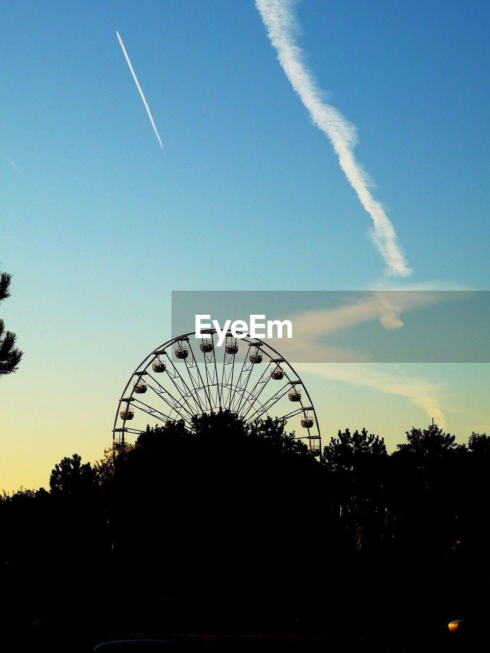 sky, tree, vapor trail, cloud - sky, nature, plant, silhouette, no people, arts culture and entertainment, amusement park, outdoors, ferris wheel, blue, amusement park ride, architecture, sunset, built structure, shape, park, environment
