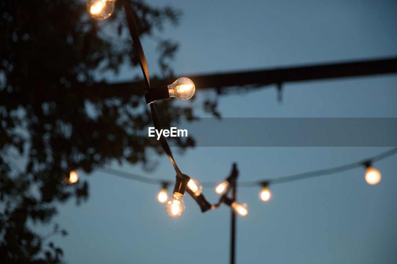 Low angle view of illuminated string light against sky at night