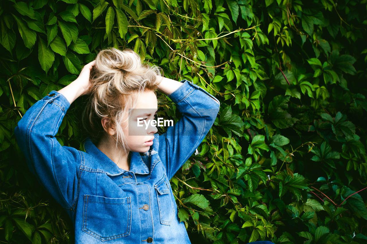 Woman Tying Hair Against Plants