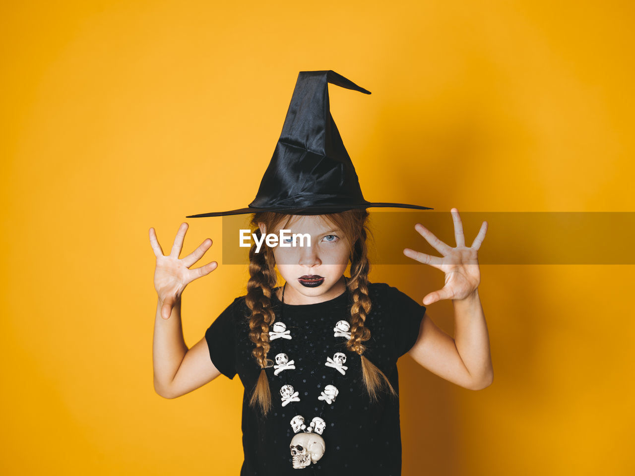 front view, looking at camera, portrait, yellow, halloween, one person, studio shot, standing, indoors, waist up, colored background, yellow background, childhood, costume, celebration, child, real people, arms raised, human arm, witch, orange background, making a face