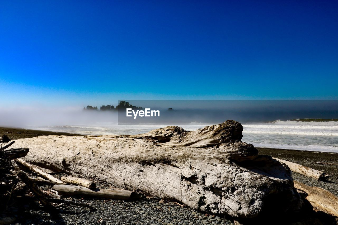 sky, blue, scenics - nature, beauty in nature, tranquil scene, tranquility, nature, copy space, day, no people, land, non-urban scene, clear sky, rock, remote, water, idyllic, environment, sunlight, solid, outdoors, driftwood