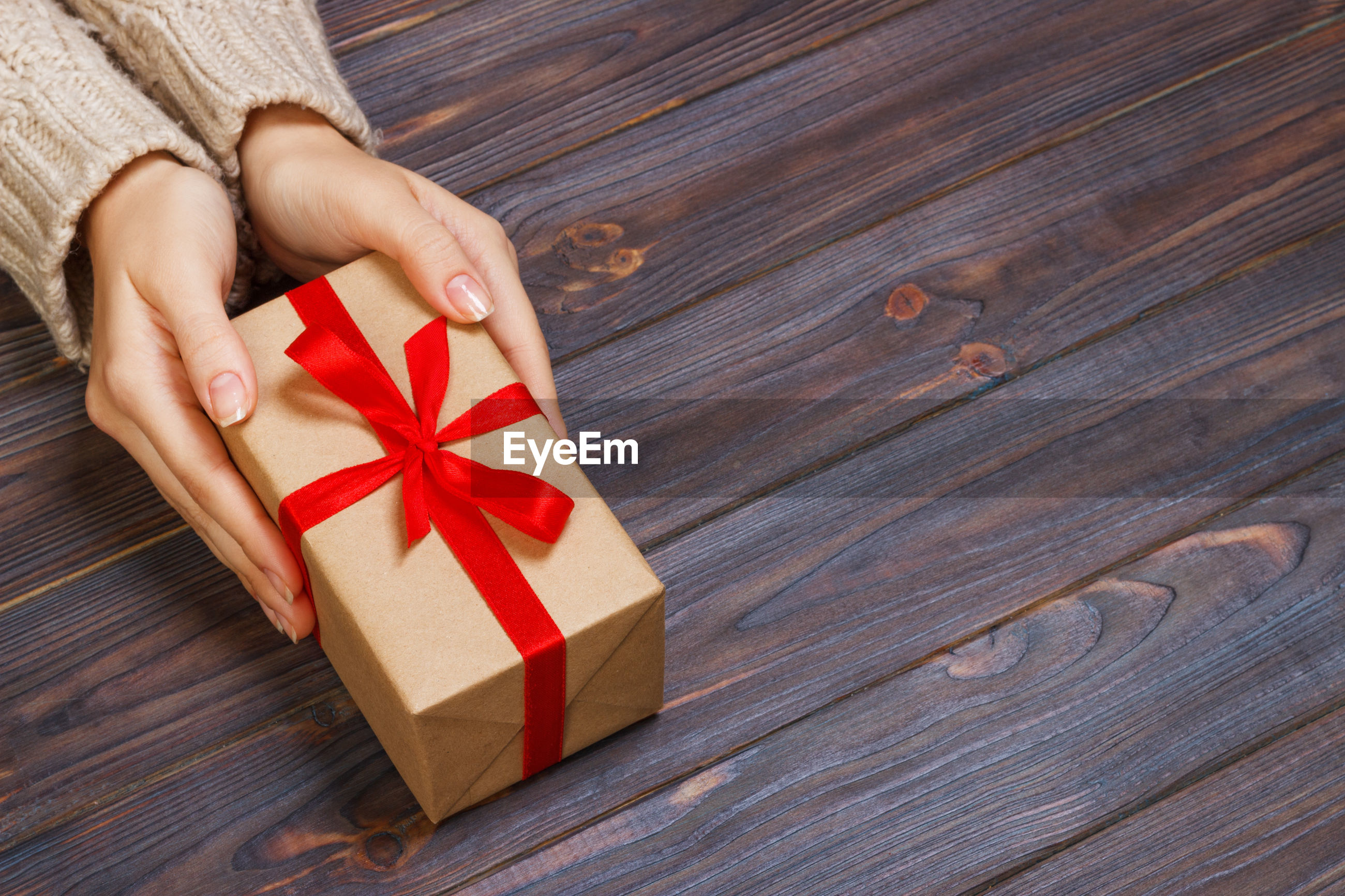 Cropped hands of woman holding gift box on wooden table