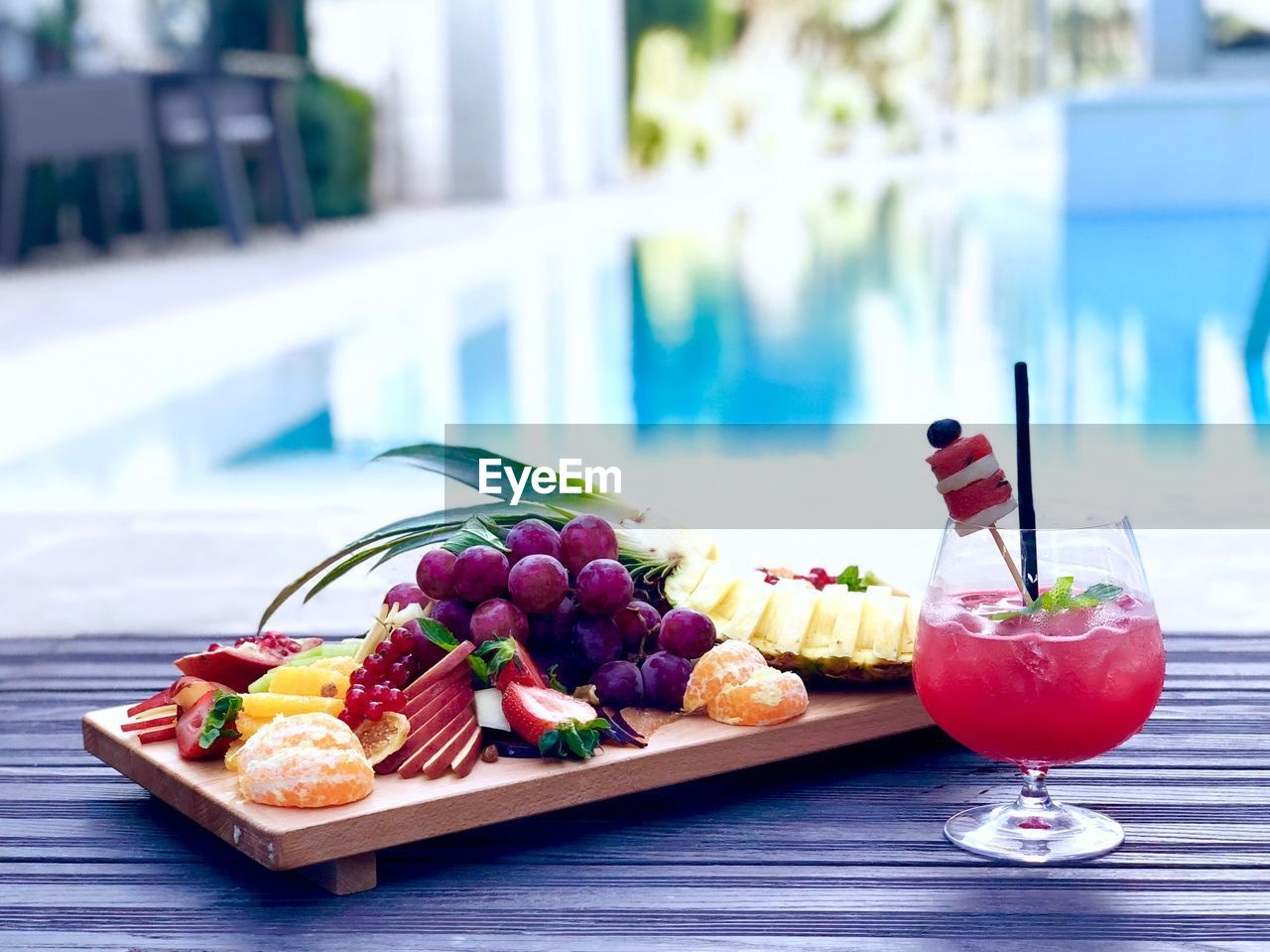 Close-up of fruits with drink on table against swimming pool